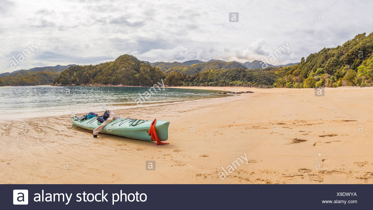 Kayak lying on the beach, Anchorage Bay, Abel Tasman National Park, Tasman Region, Southland, New Zealand - Stock Image