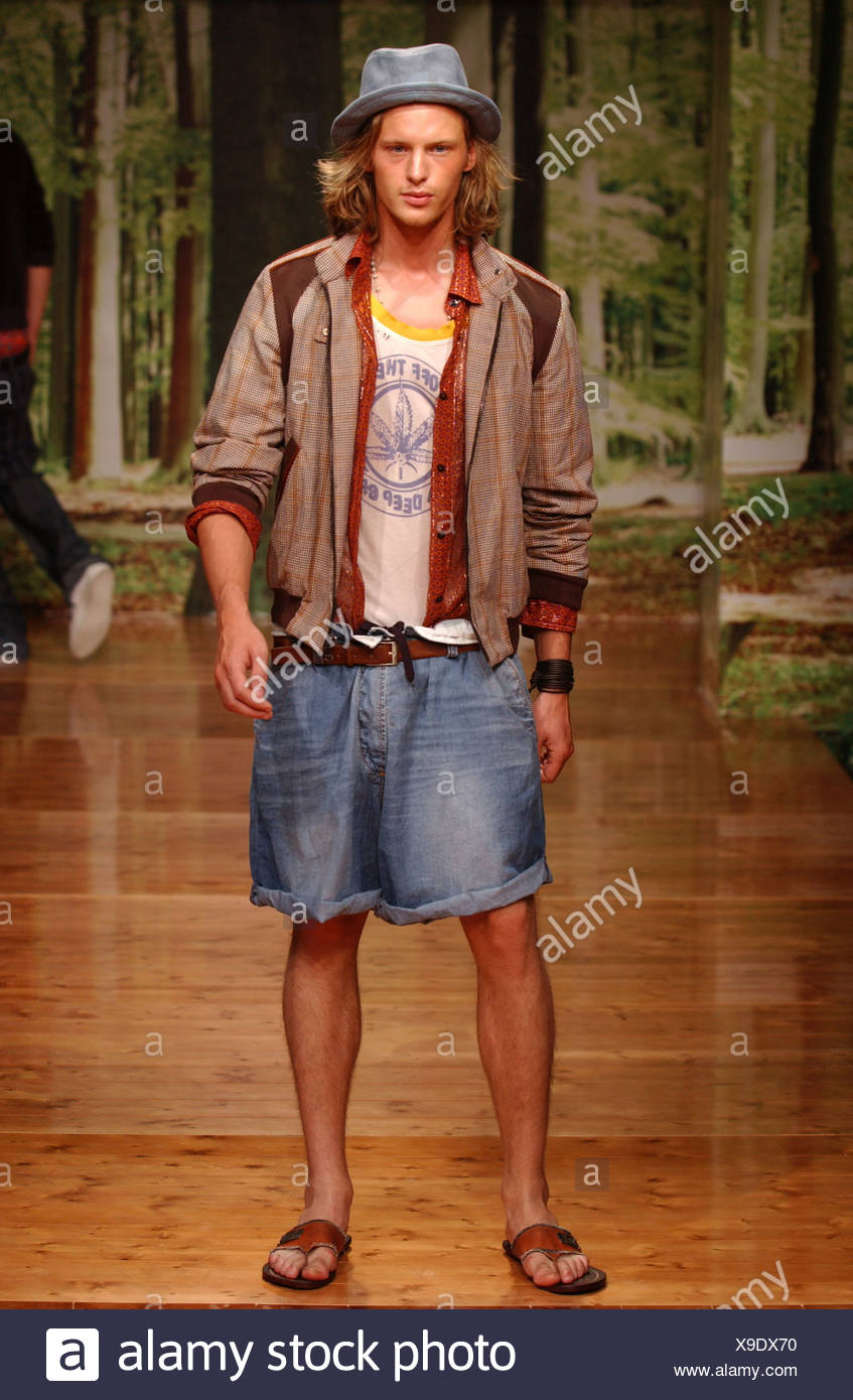 D&G Milan Menswear S S Casual wear: checked bomber jacket and baggy Bermuda jean shorts slippers Wood floand forrest setting Stock Photo
