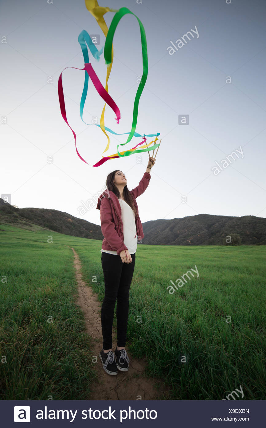 Young woman standing in field holding up dance ribbons - Stock Image