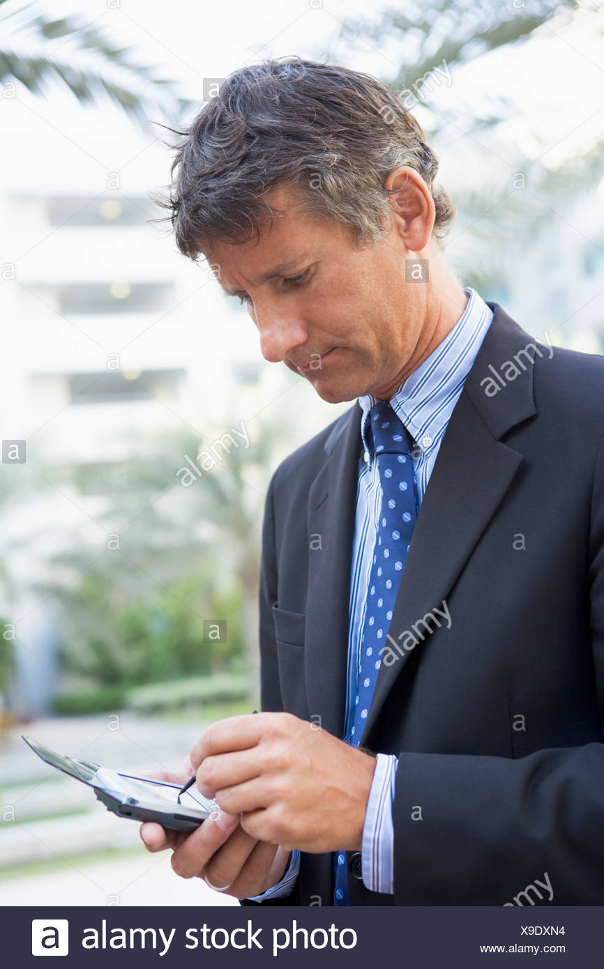 Businessman outdoors using personal digital assistant - Stock Image