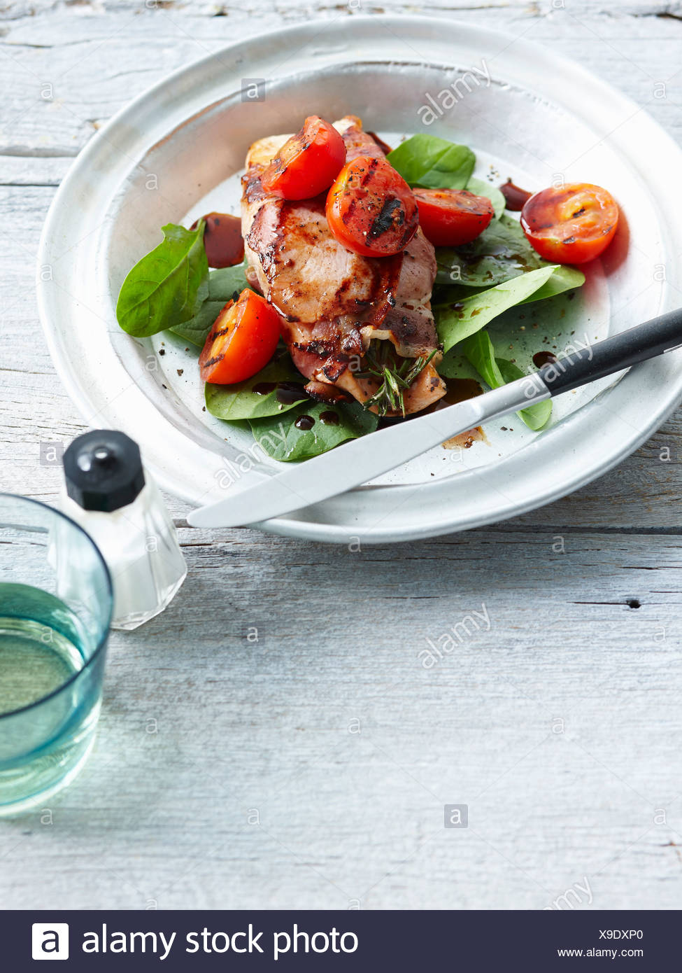Plate of chicken with grilled tomatoes - Stock Image