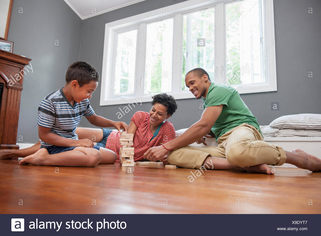 Family on the floor playing a game at home. - Stock Image