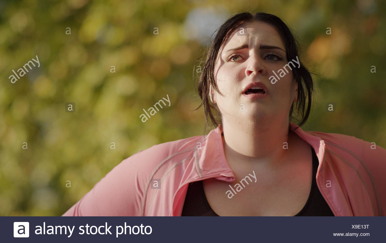 Close up of exhausted woman resting and working out outdoors - Stock Image