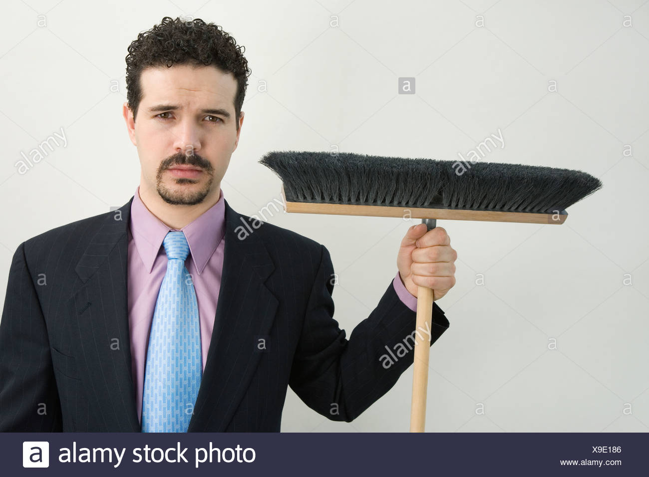 Portrait of a businessman holding a broom - Stock Image