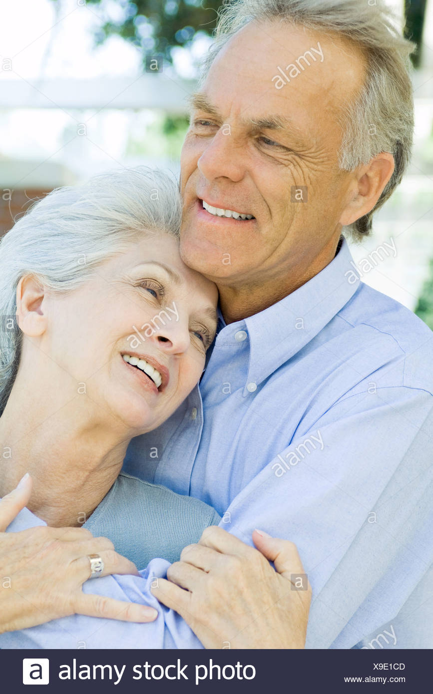 Mature couple embracing and smiling, close-up - Stock Image