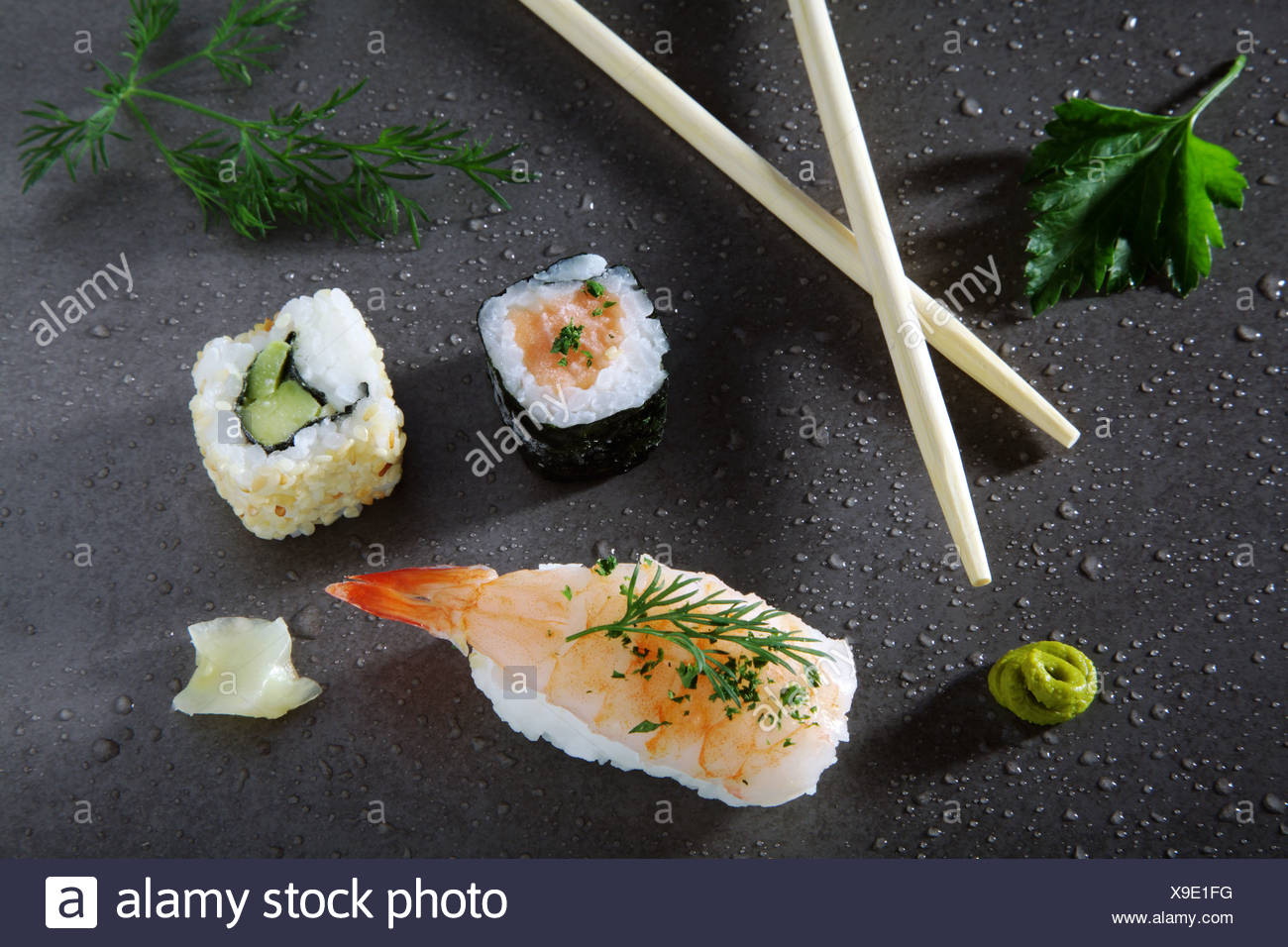 Assorted sushi with ginger and wasabi on a stone surface - Stock Image