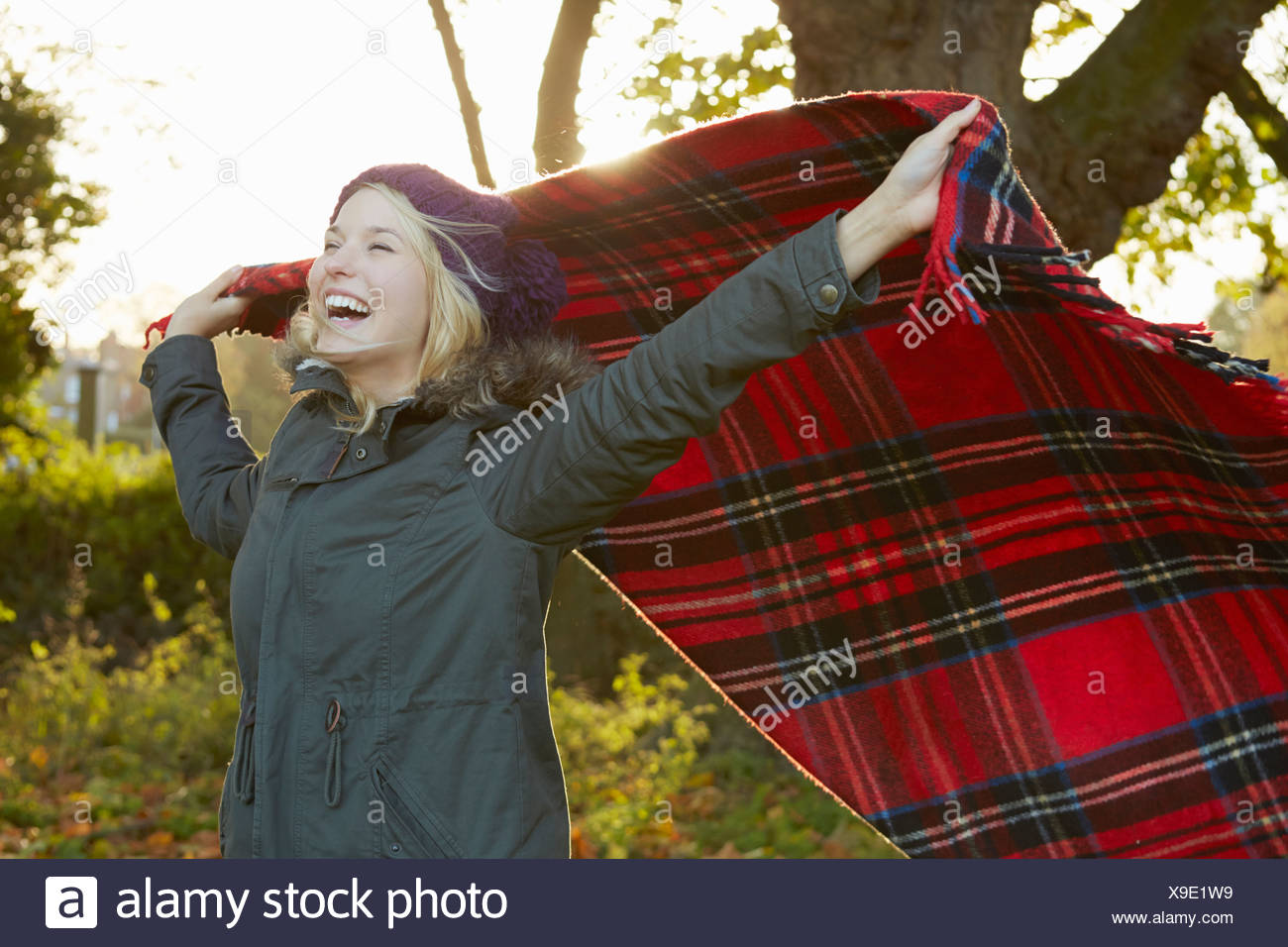 Portrait of young woman in park, holding up tartan picnic blanket - Stock Image