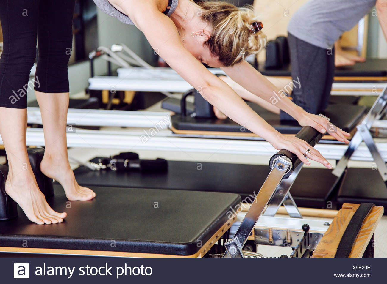Women in gym using pilates reformer - Stock Image