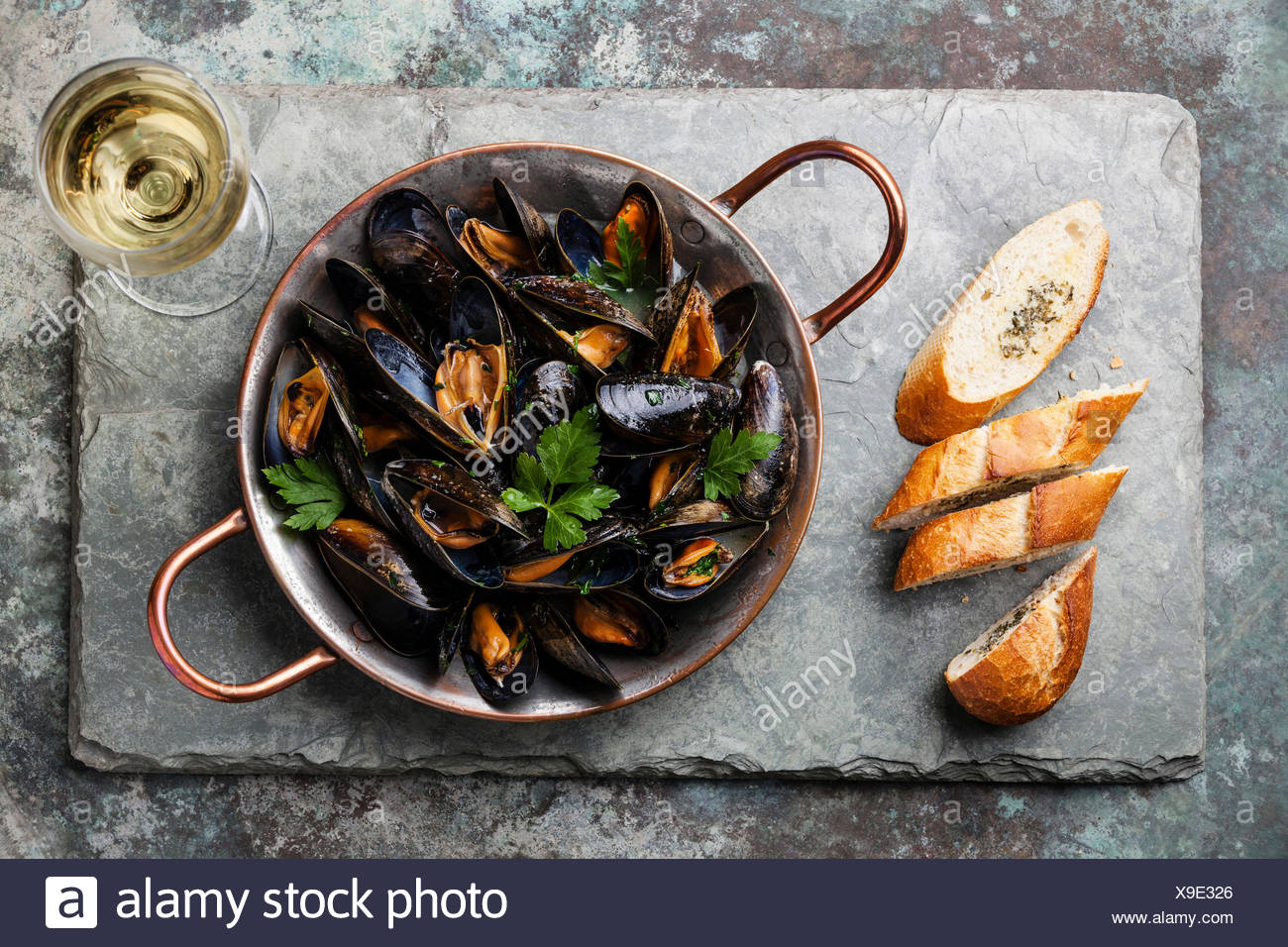 Mussels in copper cooking dish and French Baguette with herbs on stone slate background Stock Photo