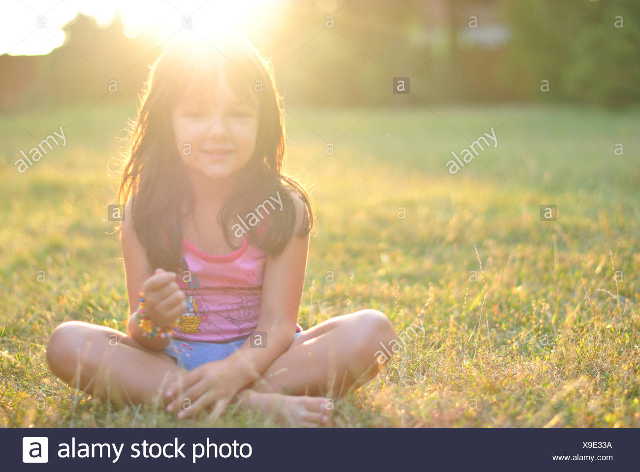 Portrait of a girl sitting cross legged on grass with sun shining on her hair - Stock Image