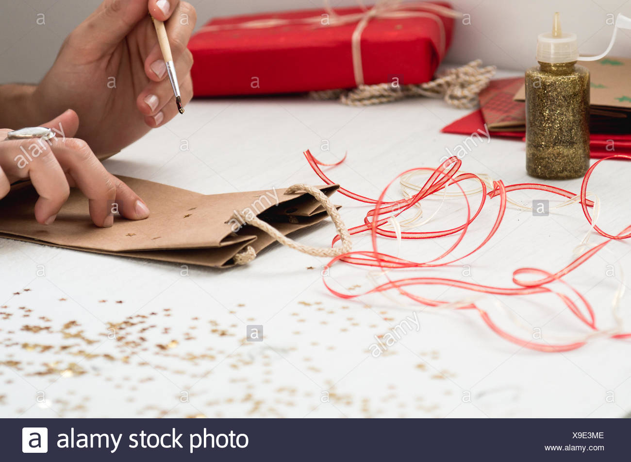 Cropped Image Of Hand Decorating Paper Bag On Table - Stock Image