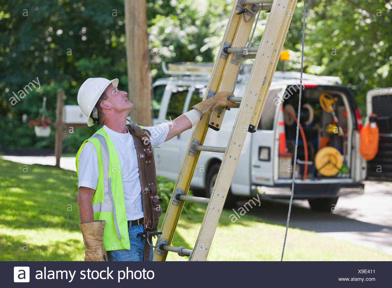 Communications worker preparing to climb ladder for overhead wiring - Stock Image