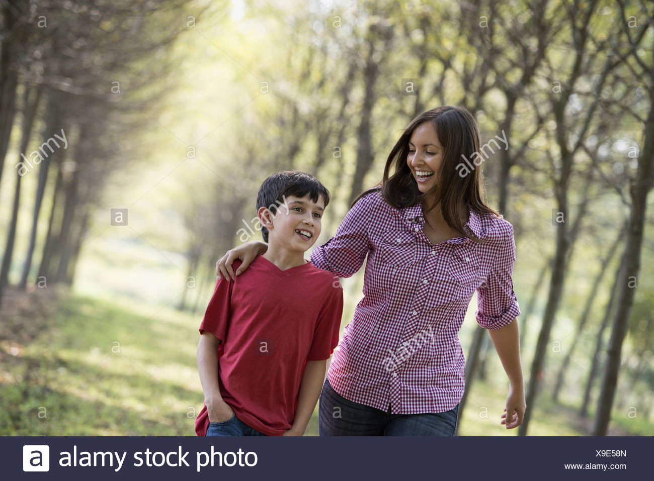 A woman and a child walking down an avenue of trees. - Stock Image