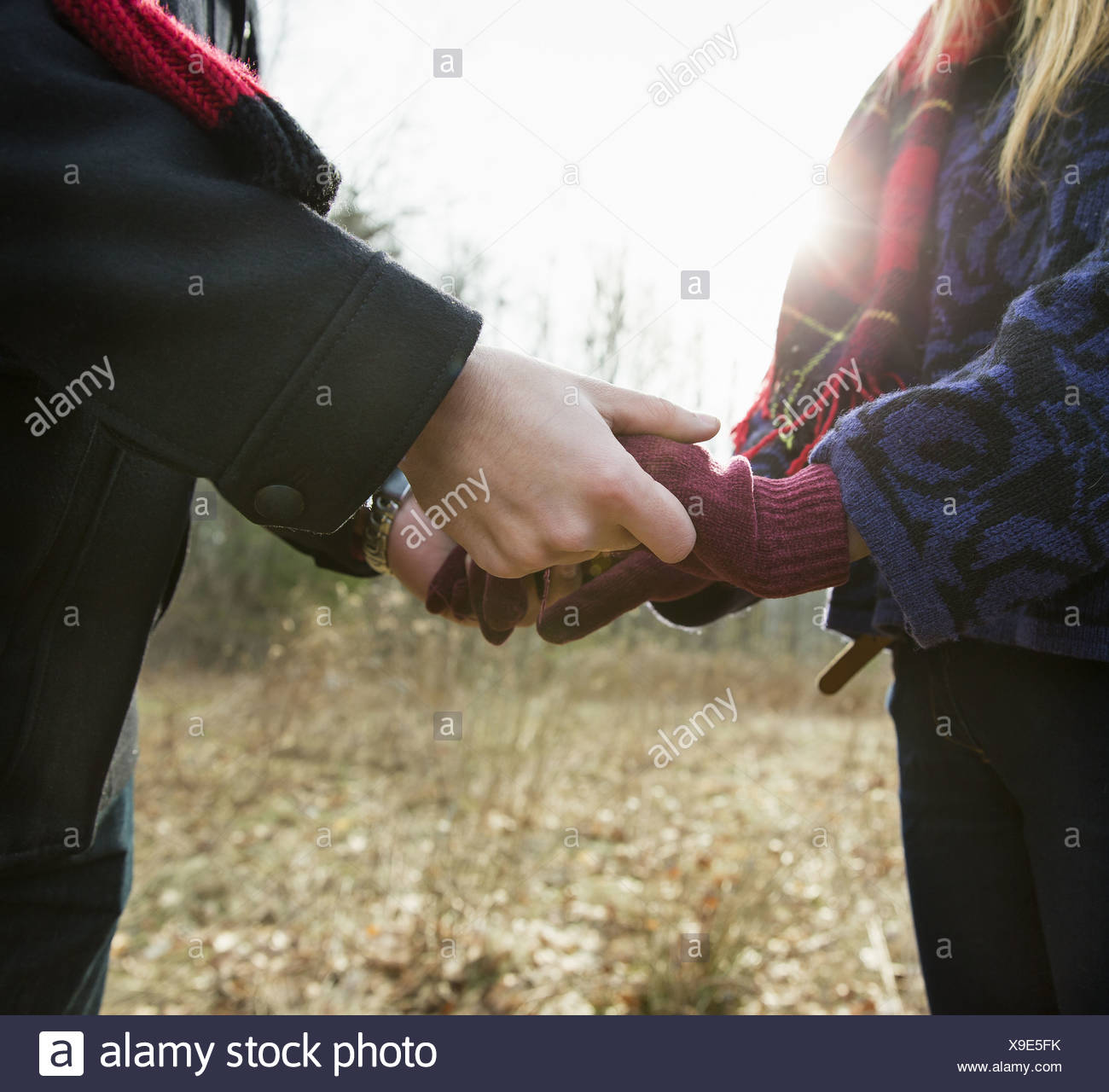 A couple in winter coats, outdoors on a winter's day. Holding hands. - Stock Image