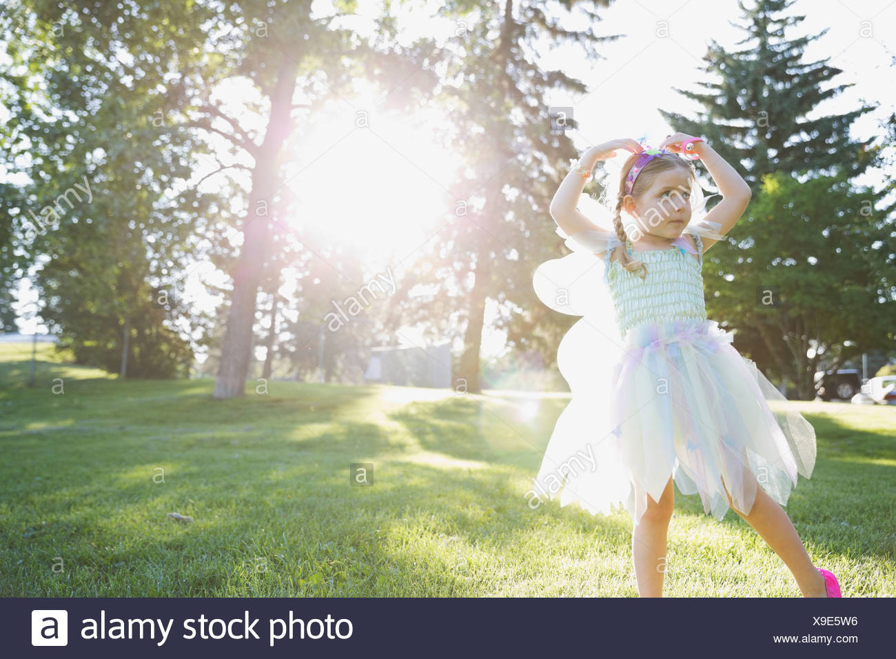 Little girl wearing fairy costume dancing in park - Stock Image