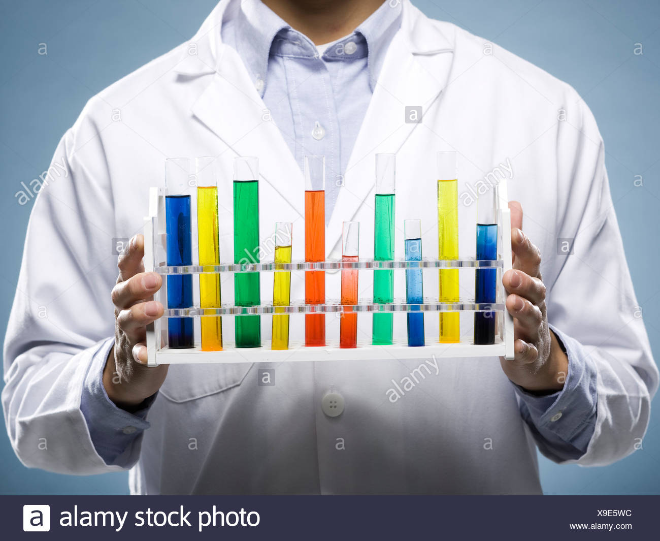 scientist holding test tubes - Stock Image