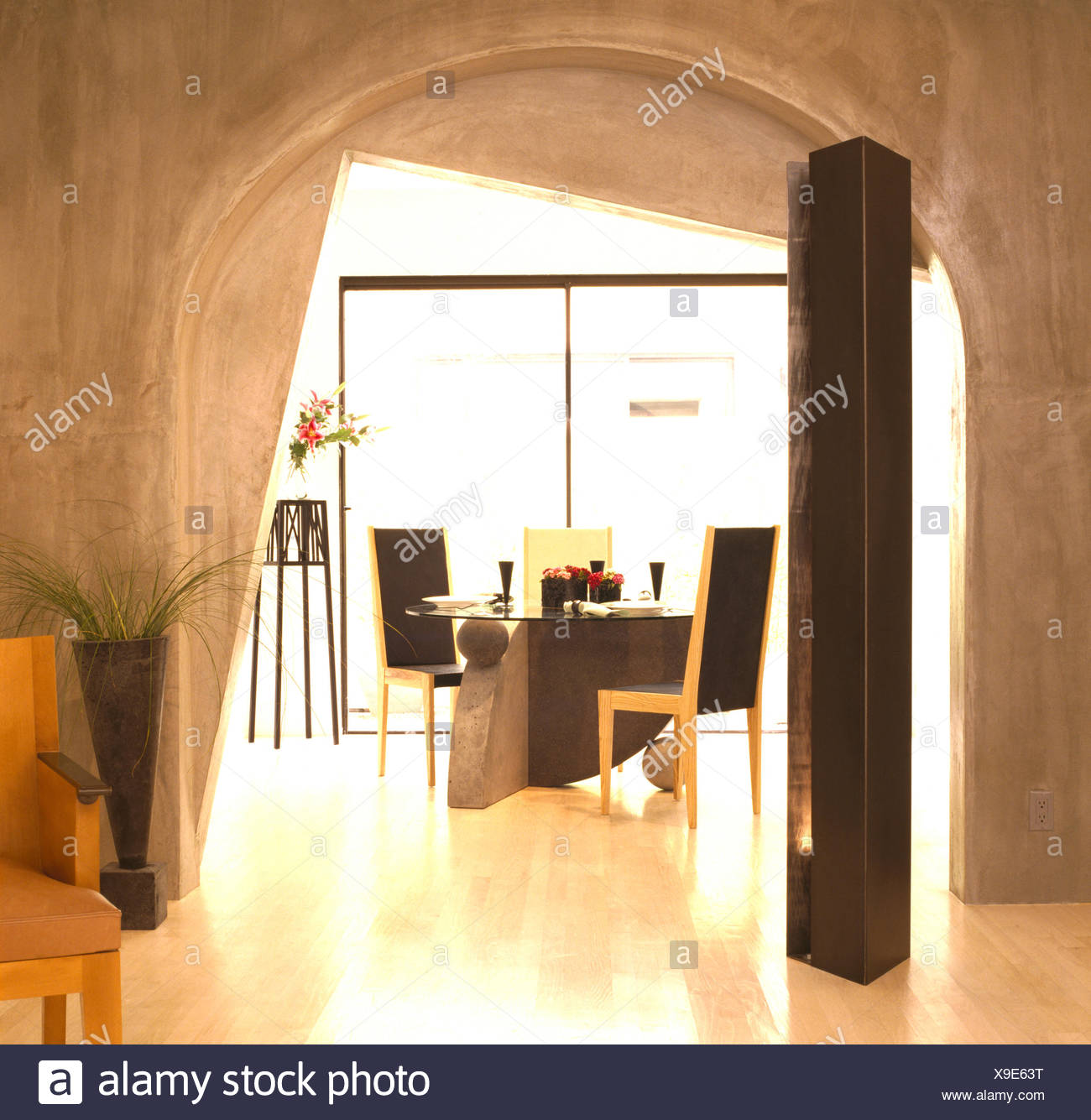 Concrete walls and polished floor in dining area with arched doorway and tall speaker in late eighties Californian house - Stock Image
