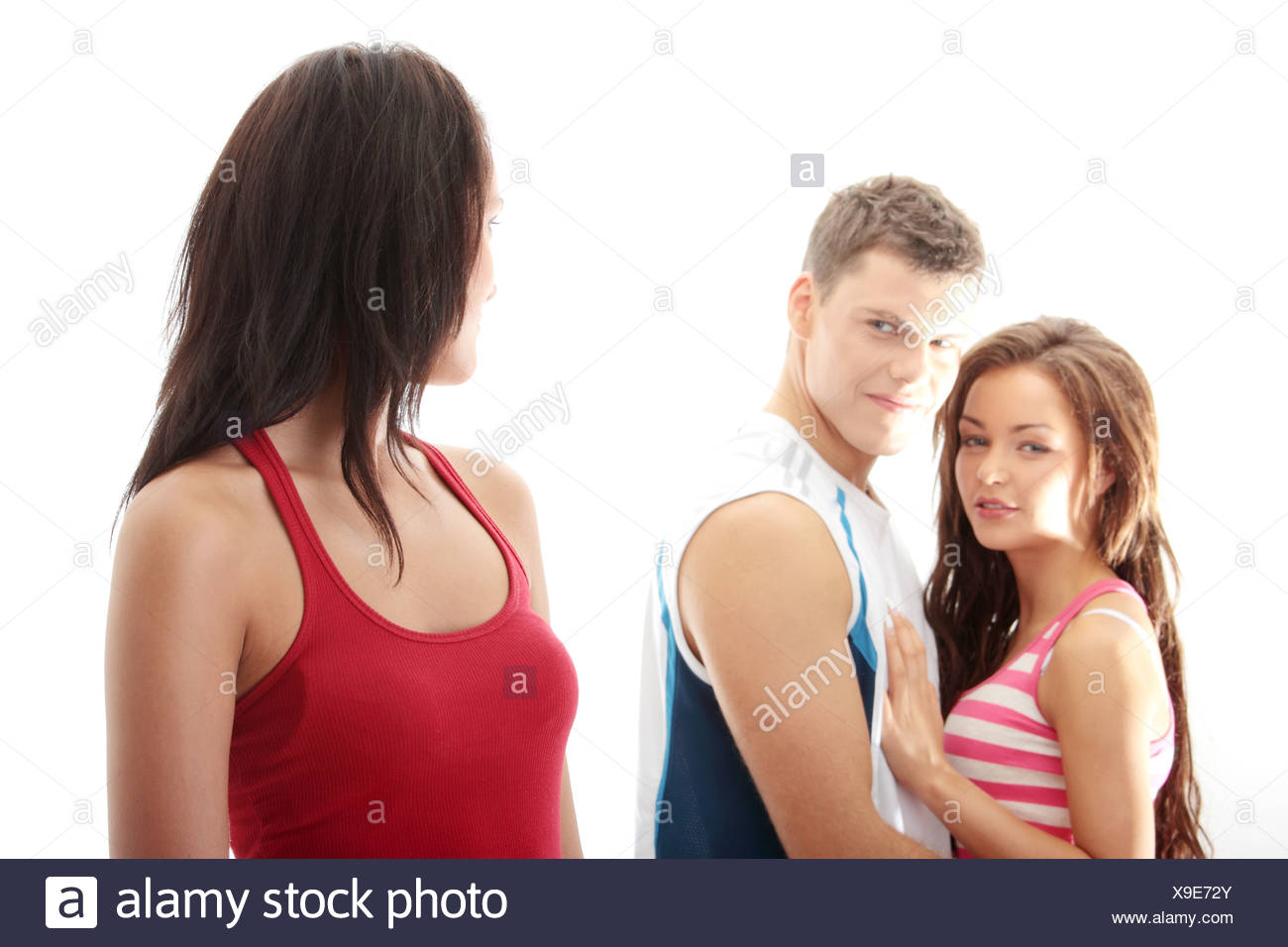 Unfaithful boyfriend concept. Boyfriend is flirting with another girl. Isolated on white background - Stock Image