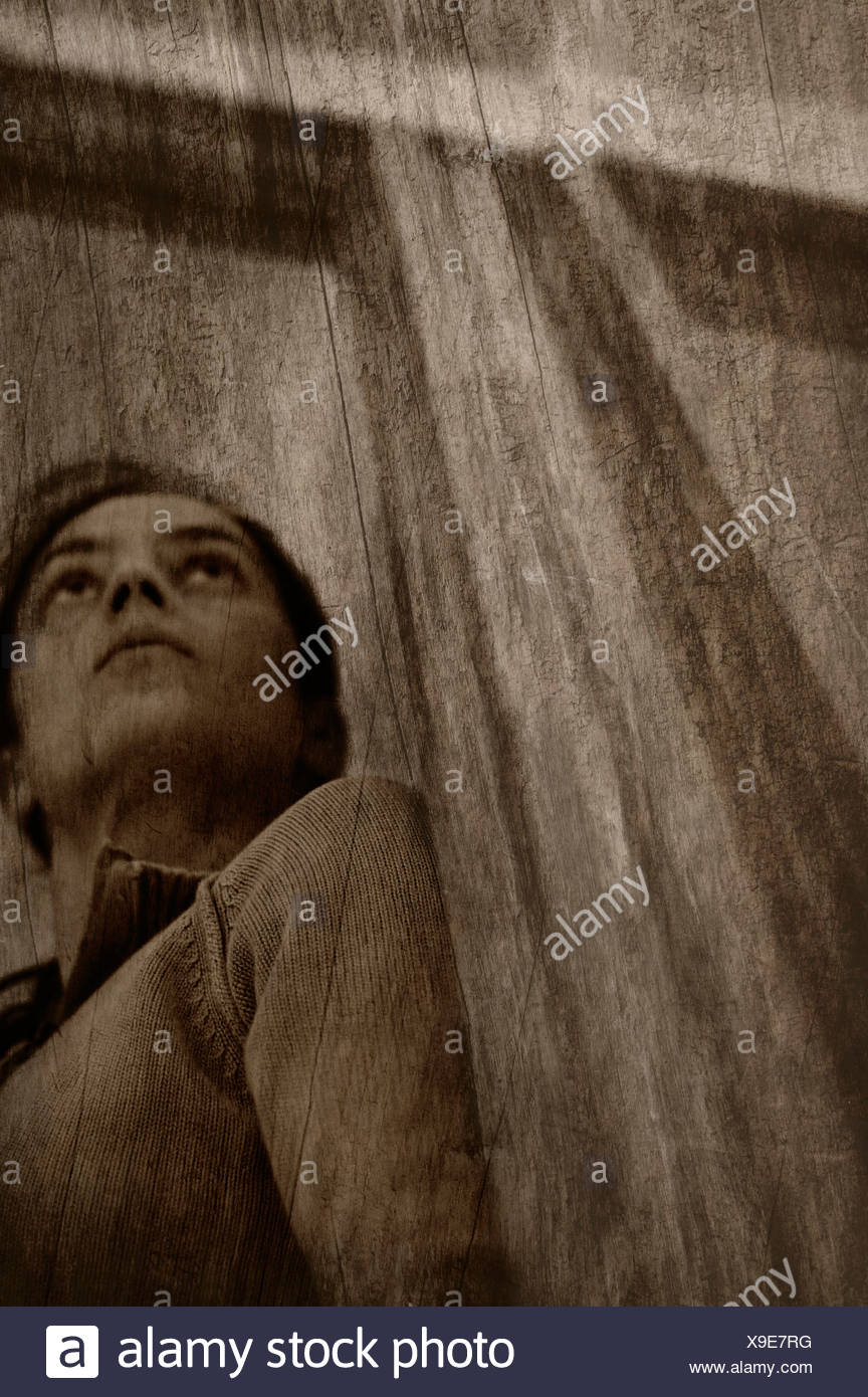 Looking up at a woman who stands hiding in a doorway - Stock Image
