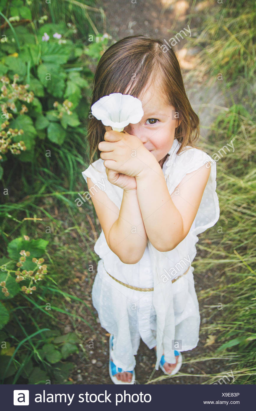 Girl holding a flower in front of her face - Stock Image