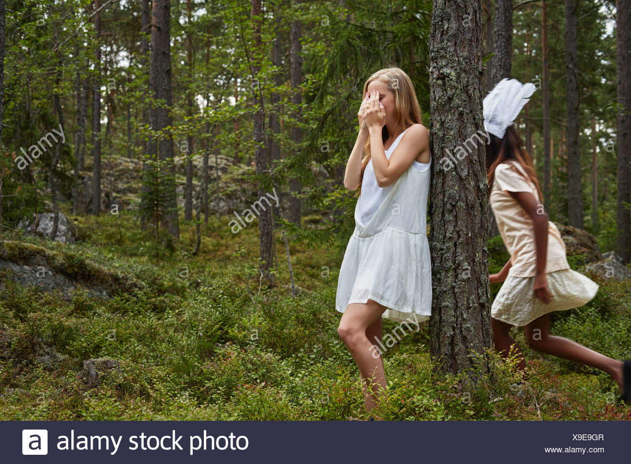 Teenage girls playing hide and seek in forest Stock Photo