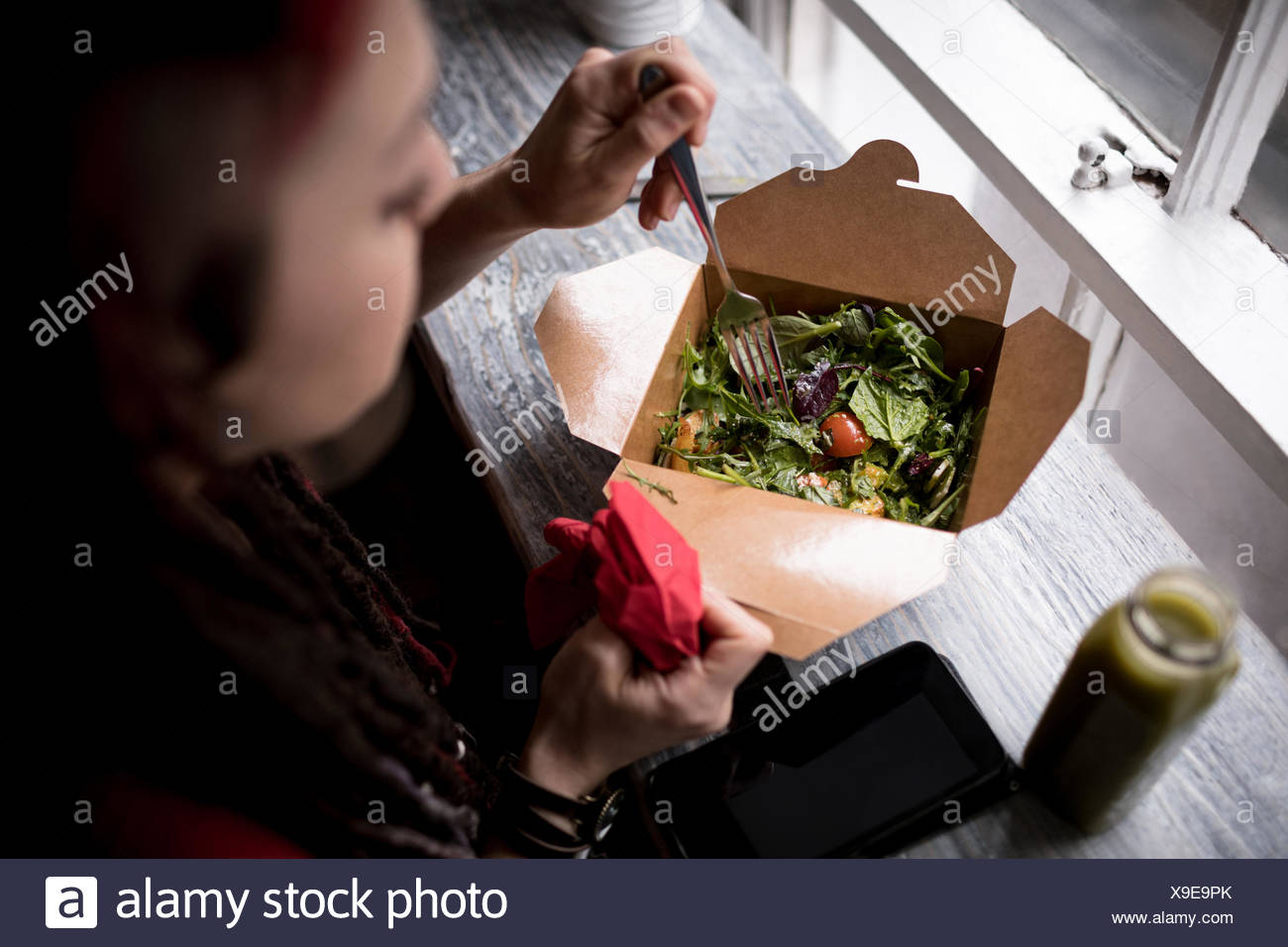 Beautiful woman having a salad in café - Stock Image