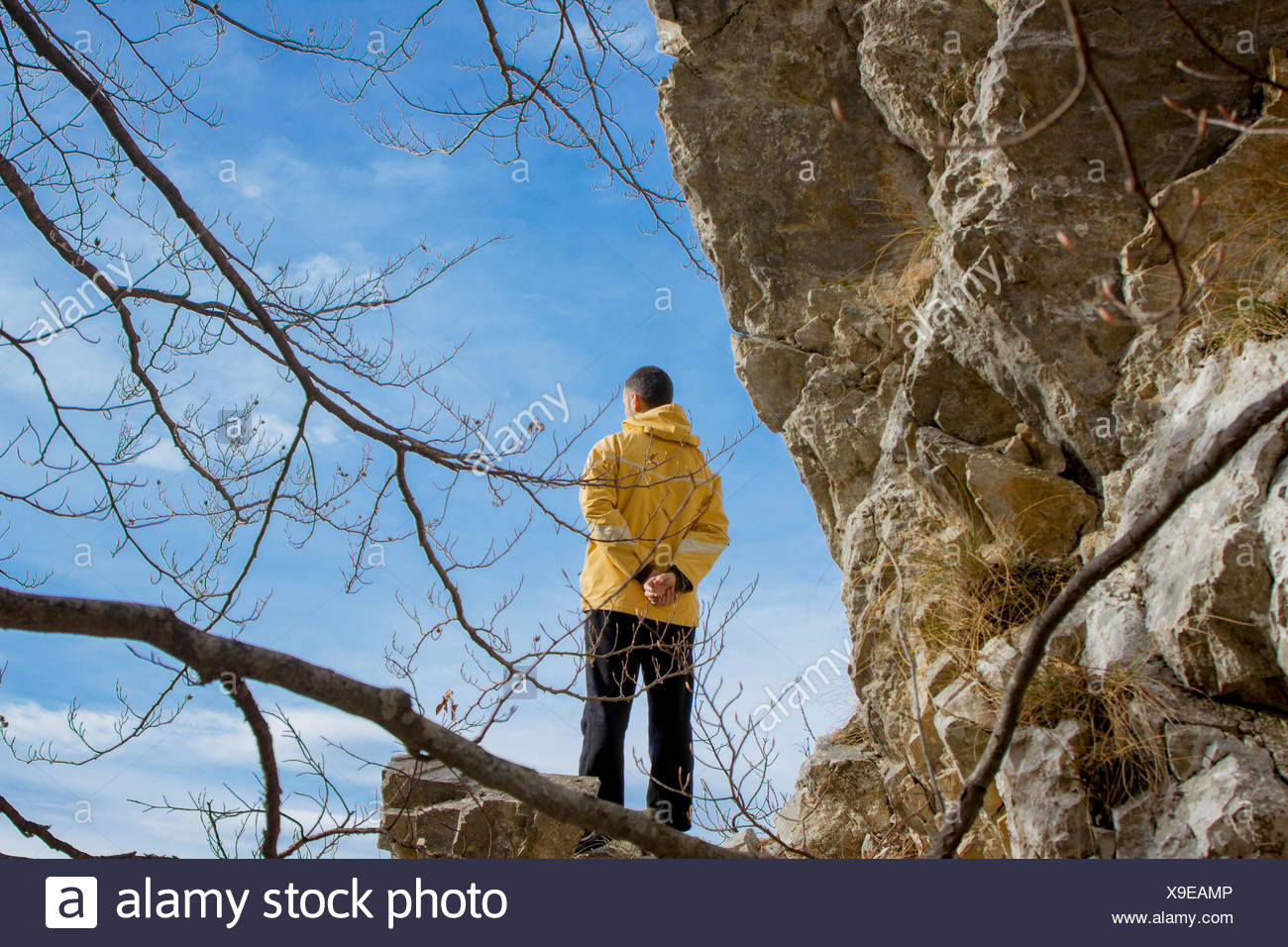Hiker standing on the edge of a cliff and looking ahead - Stock Image
