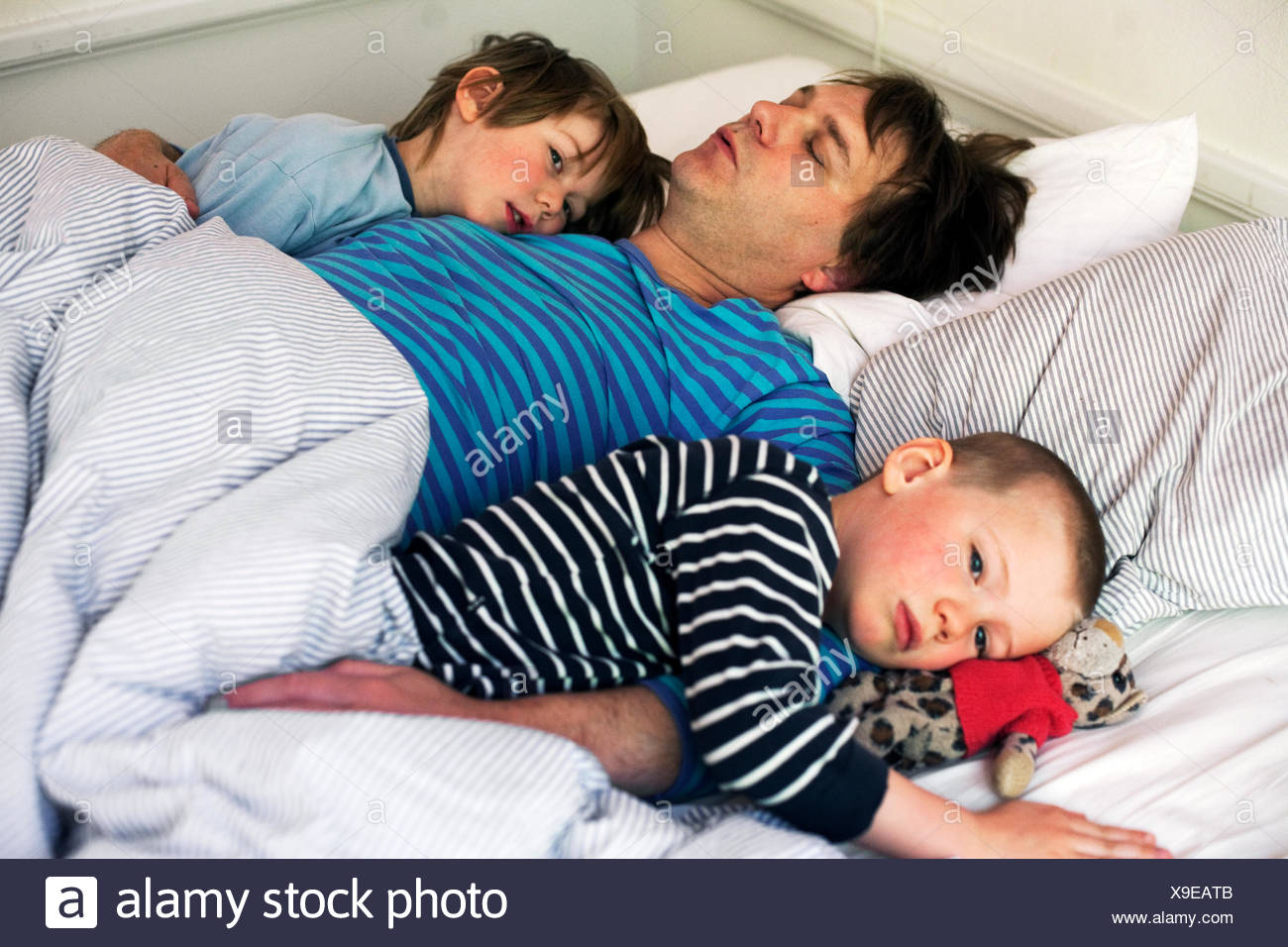 family of three people sleeping in one bed stock photos family of