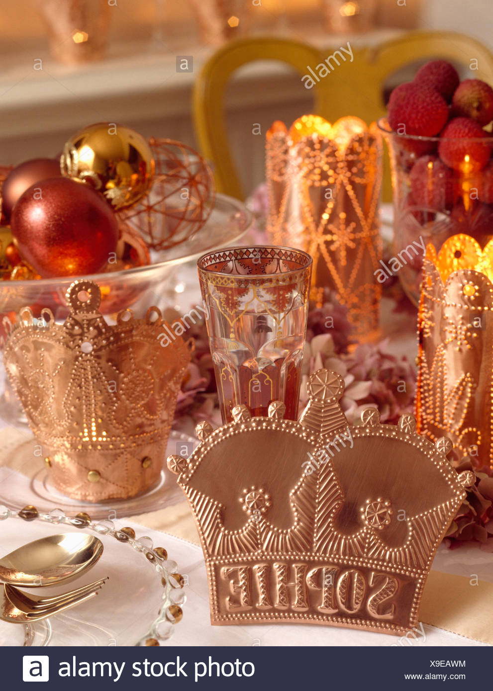Copper placenames on table with candles and metallic baubles - Stock Image