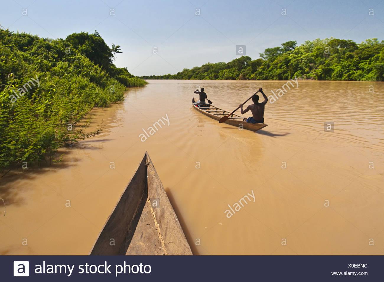 Black Volta river Ghana Men paddling canoe upstream Black Voltriver Ghana - Stock Image