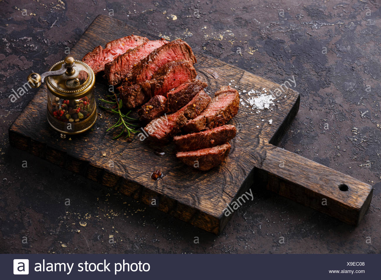 Sliced medium rare grilled Beef steak and pepper mill on wooden cutting board - Stock Image