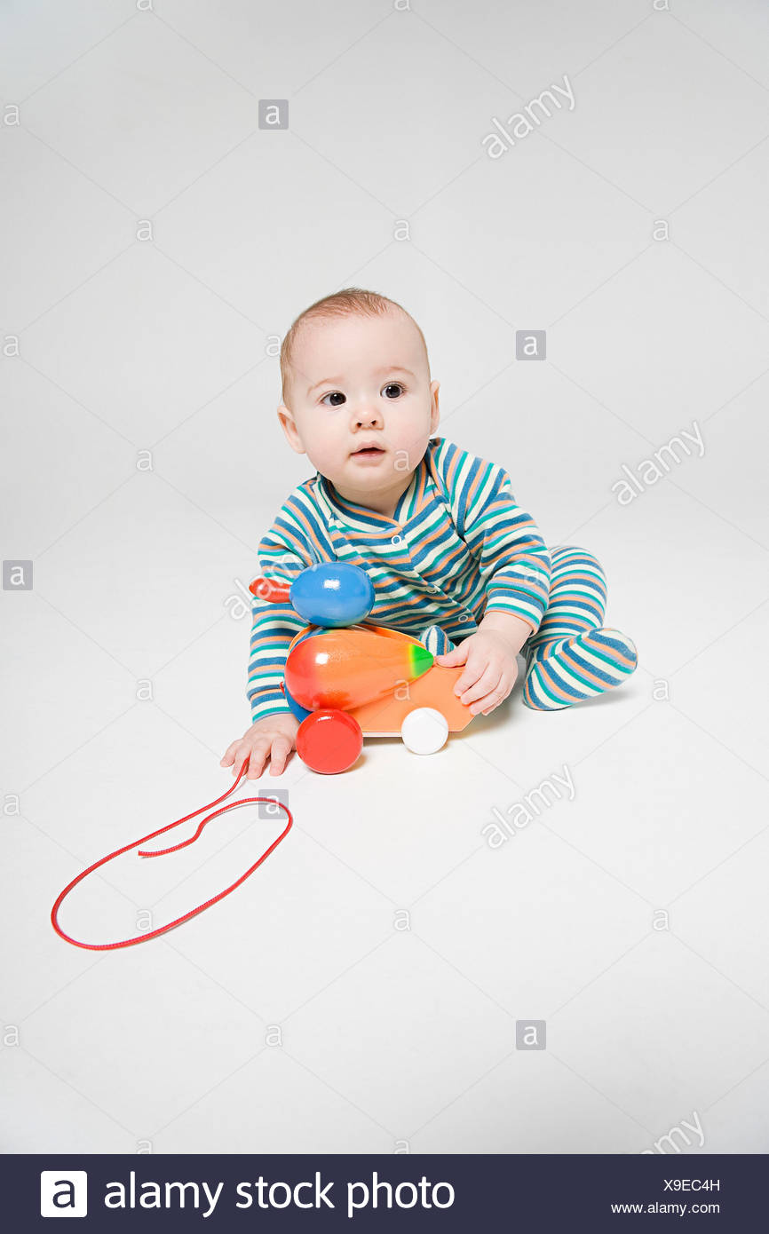 A baby boy playing with a toy - Stock Image