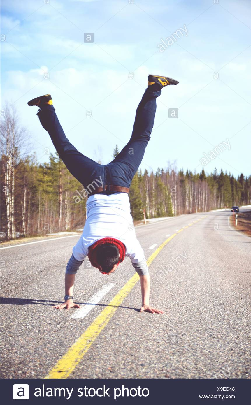 Full Length Rear View Of Man Doing Handstand On Country Road Against Cloudy Sky - Stock Image