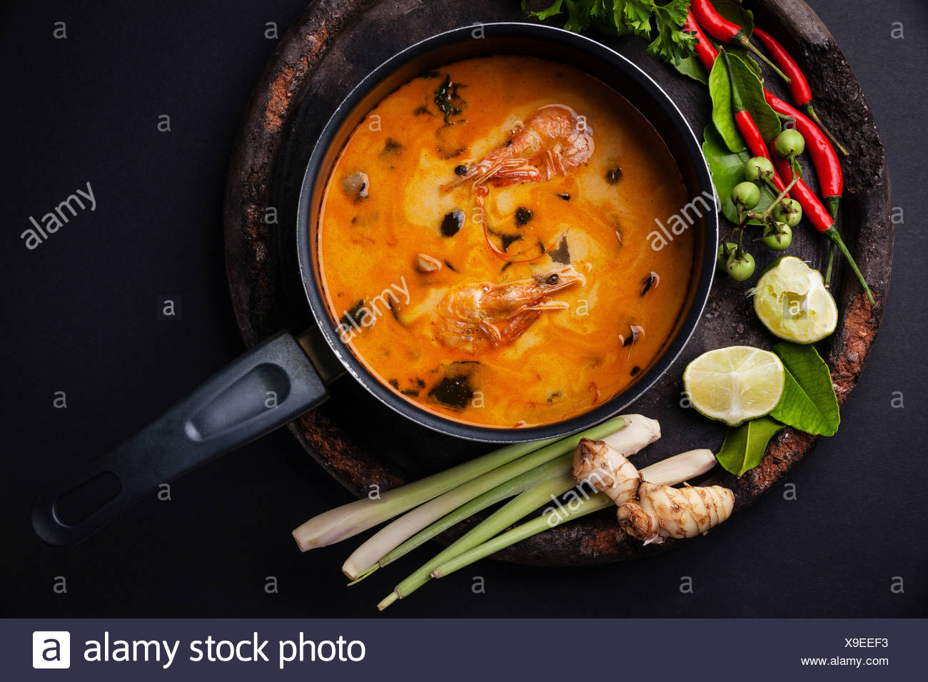 Spicy Thai soup Tom Yam with Ingredients on dark background - Stock Image