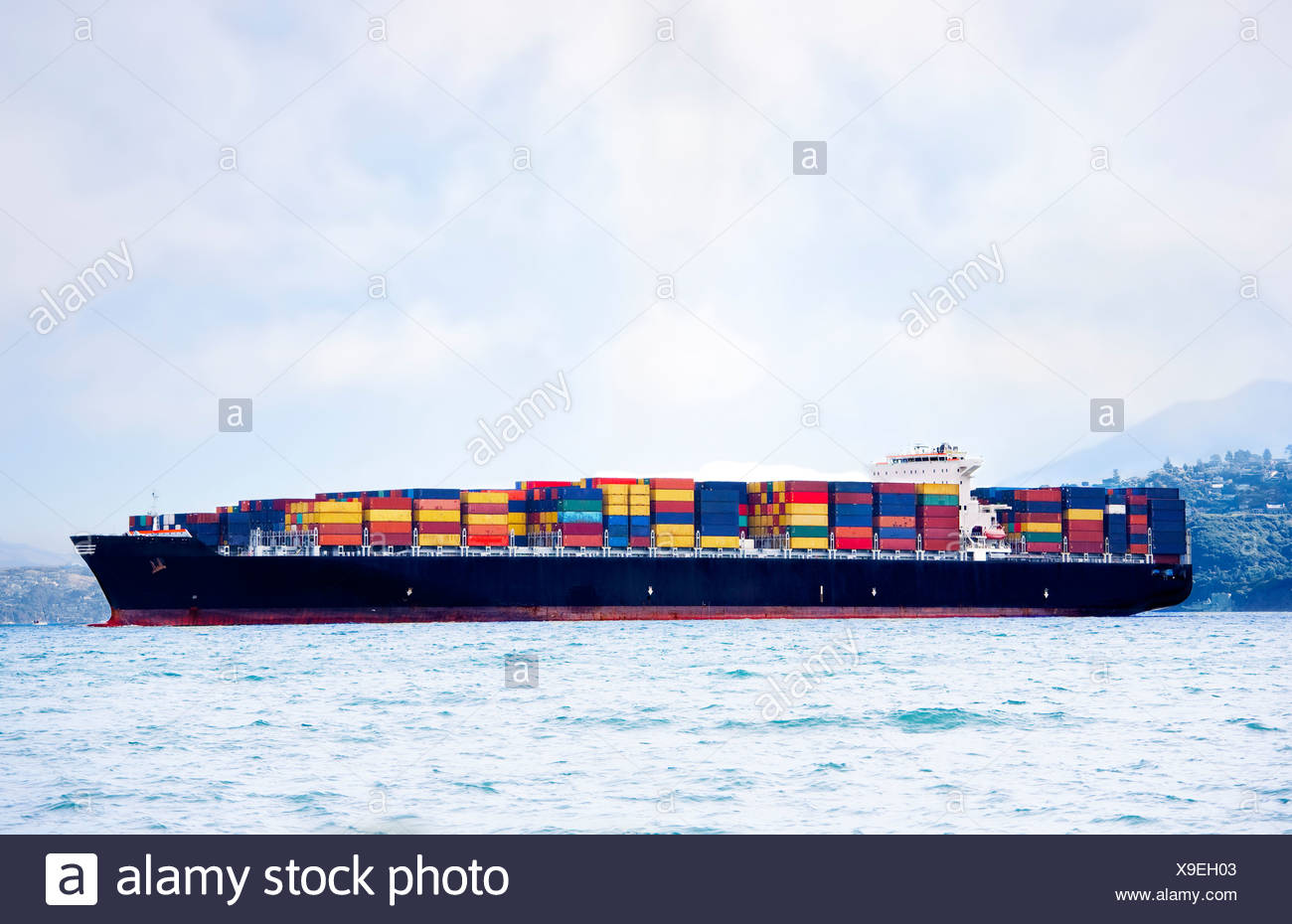 Large cargo ship in water carrying colorful shipping containers - Stock Image