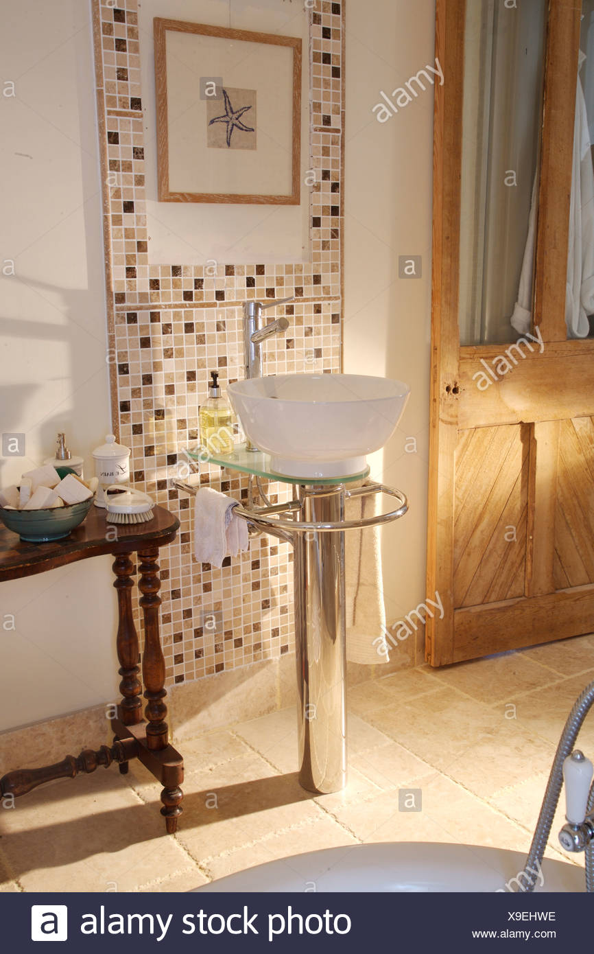 Modern wash basin on chrome pedestal in country bathroom with mosaic tiling and antique side table Stock Photo