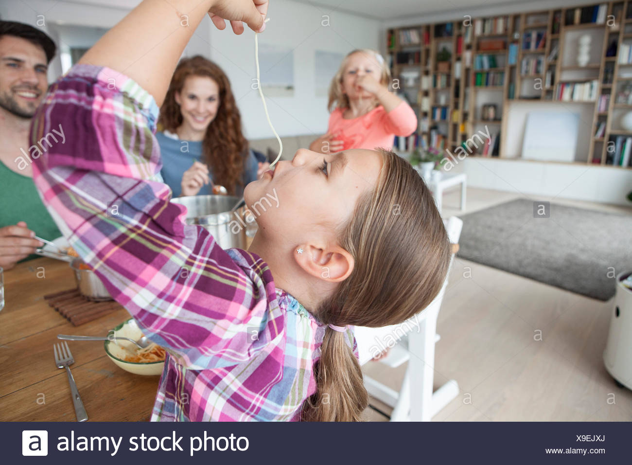 Little girl eating spaghetti while her parents and sister watching her - Stock Image