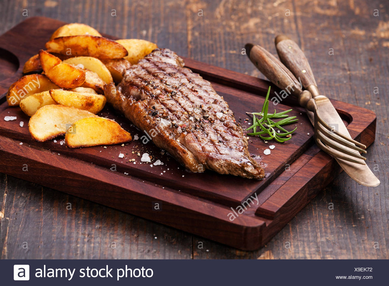 Well done grilled New York steak with roasted potato wedges on cutting board on dark wooden background - Stock Image