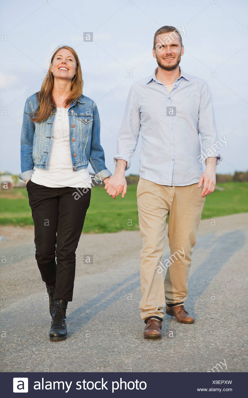 Full length of beautiful couple holding hands - Stock Image