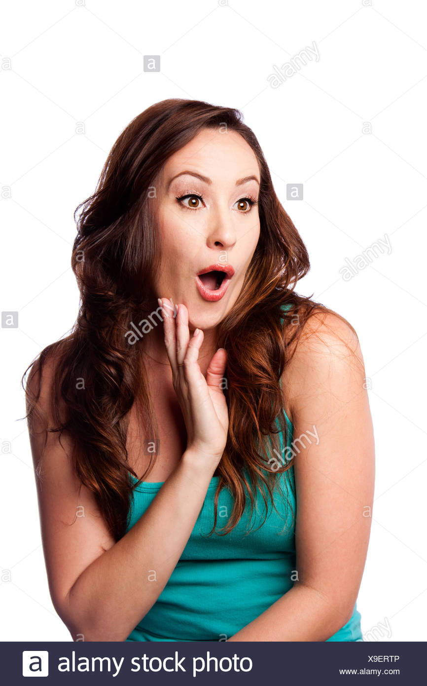 Facial expression of a Surprised shocked amazed young woman with hand on chin and long wavy brown hair, isolated. - Stock Image