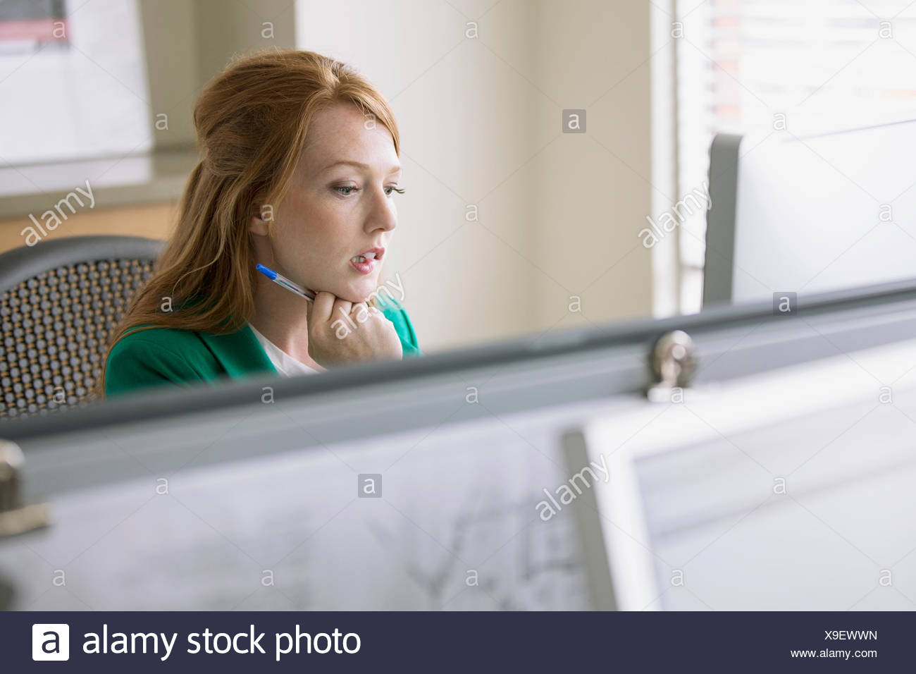 pretty office worker biting her lip - Stock Image