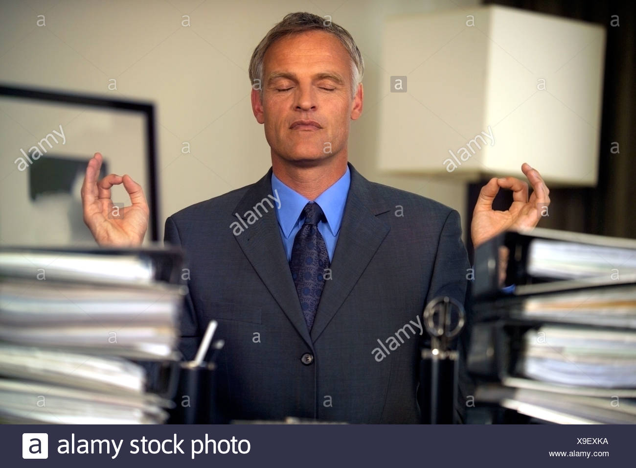 calm businessman meditating at desk with piles of folders and paperwork - Stock Image