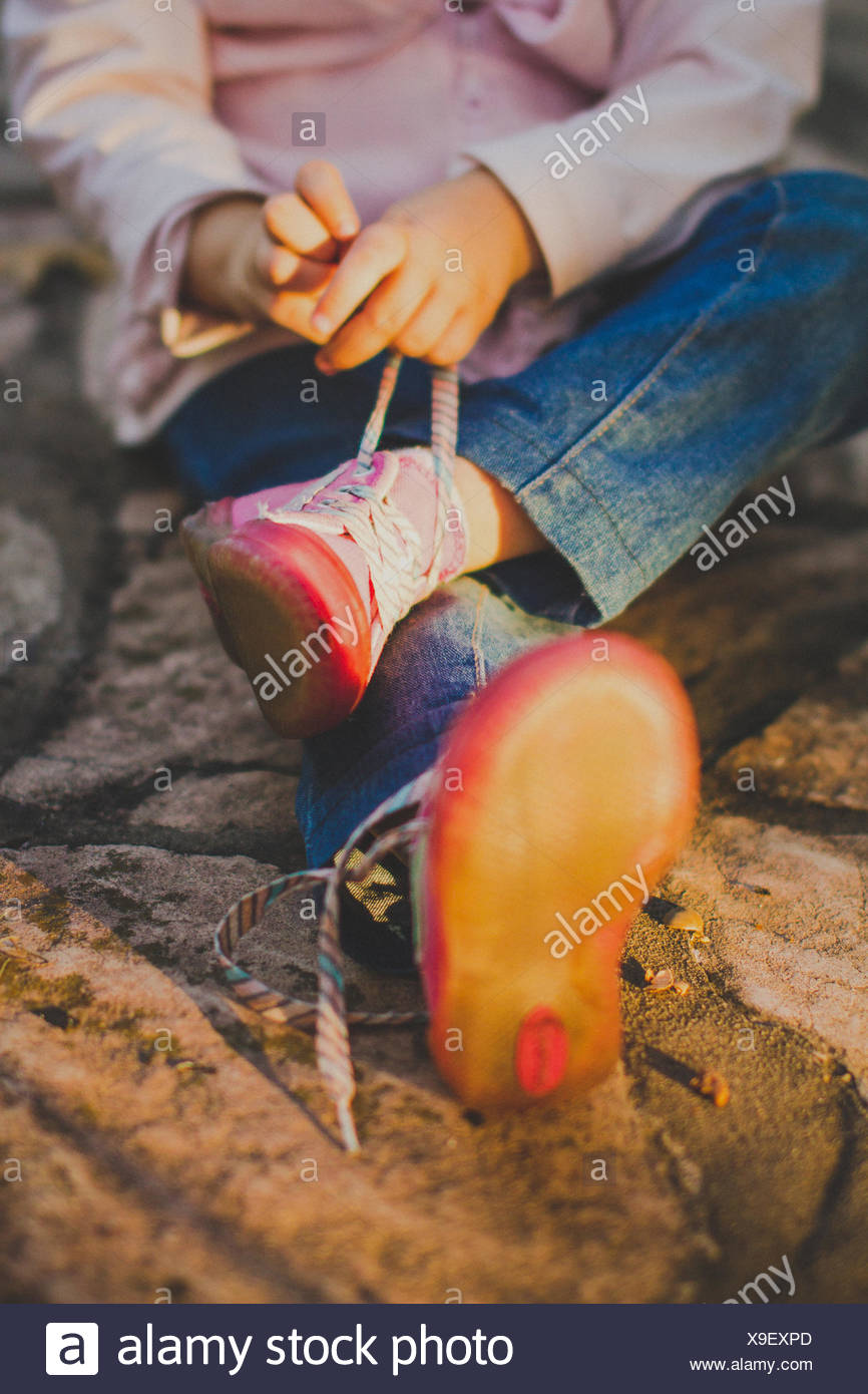 Cropped shot of girl (2-3) tying shoelaces - Stock Image