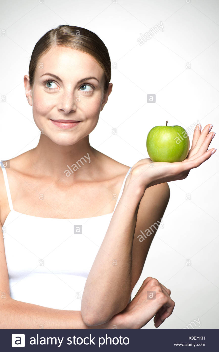 Young woman holding up green apple - Stock Image