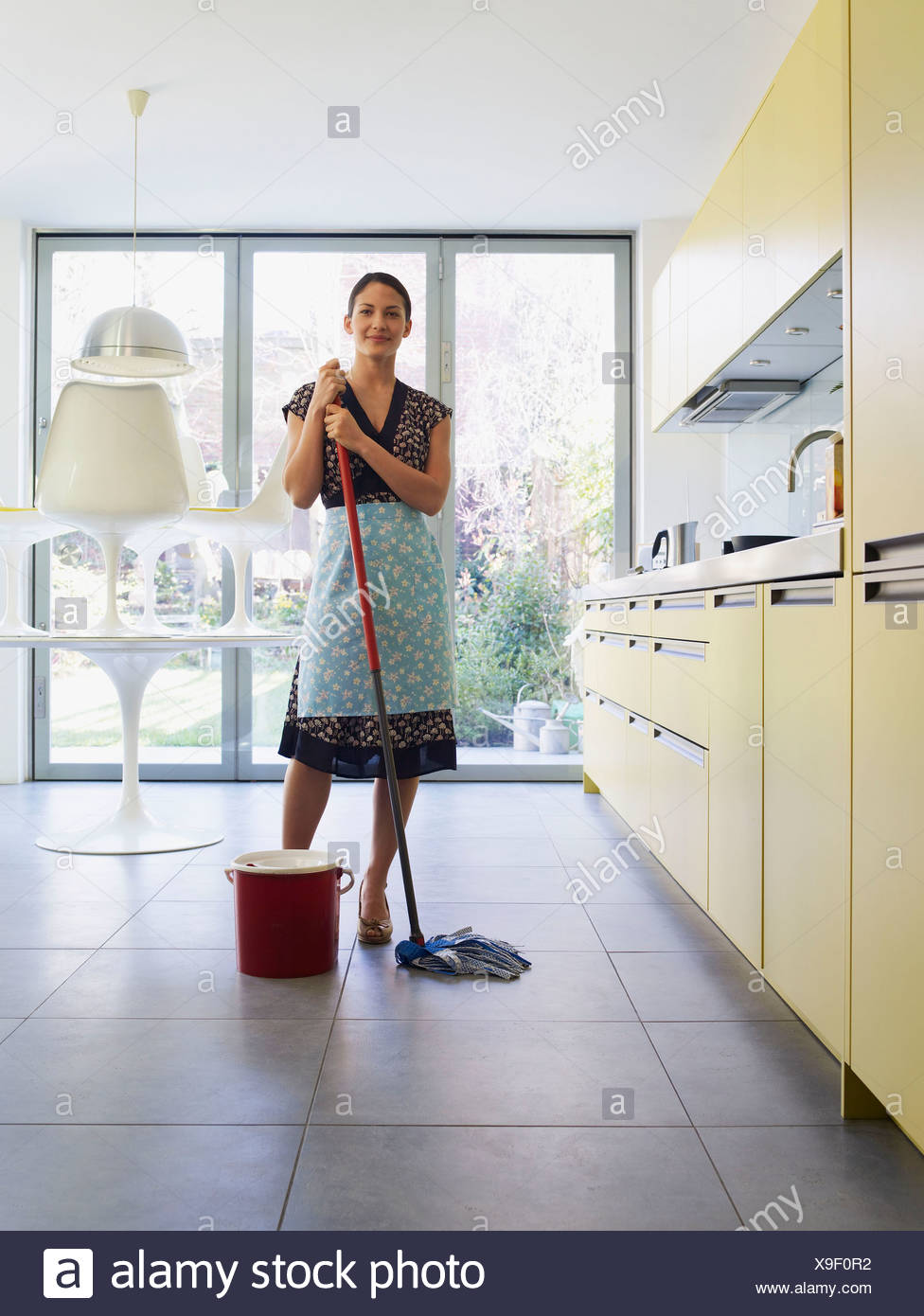 Young woman with mop in kitchen - Stock Image