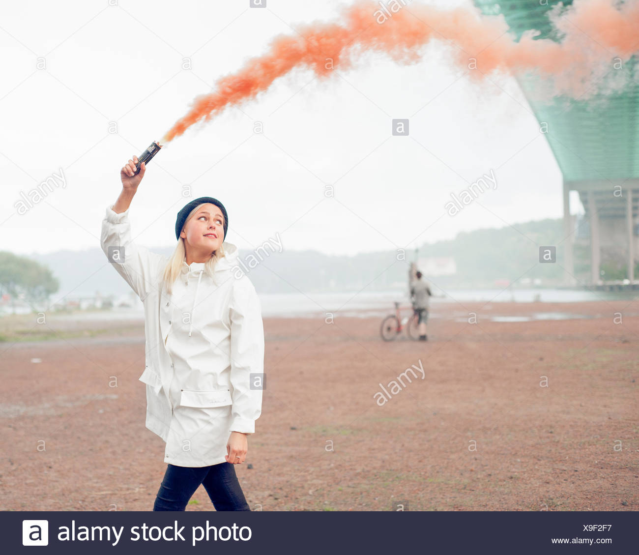 Sweden, Vastra Gotaland, Gothenburg, Young woman walking with distress flare Stock Photo