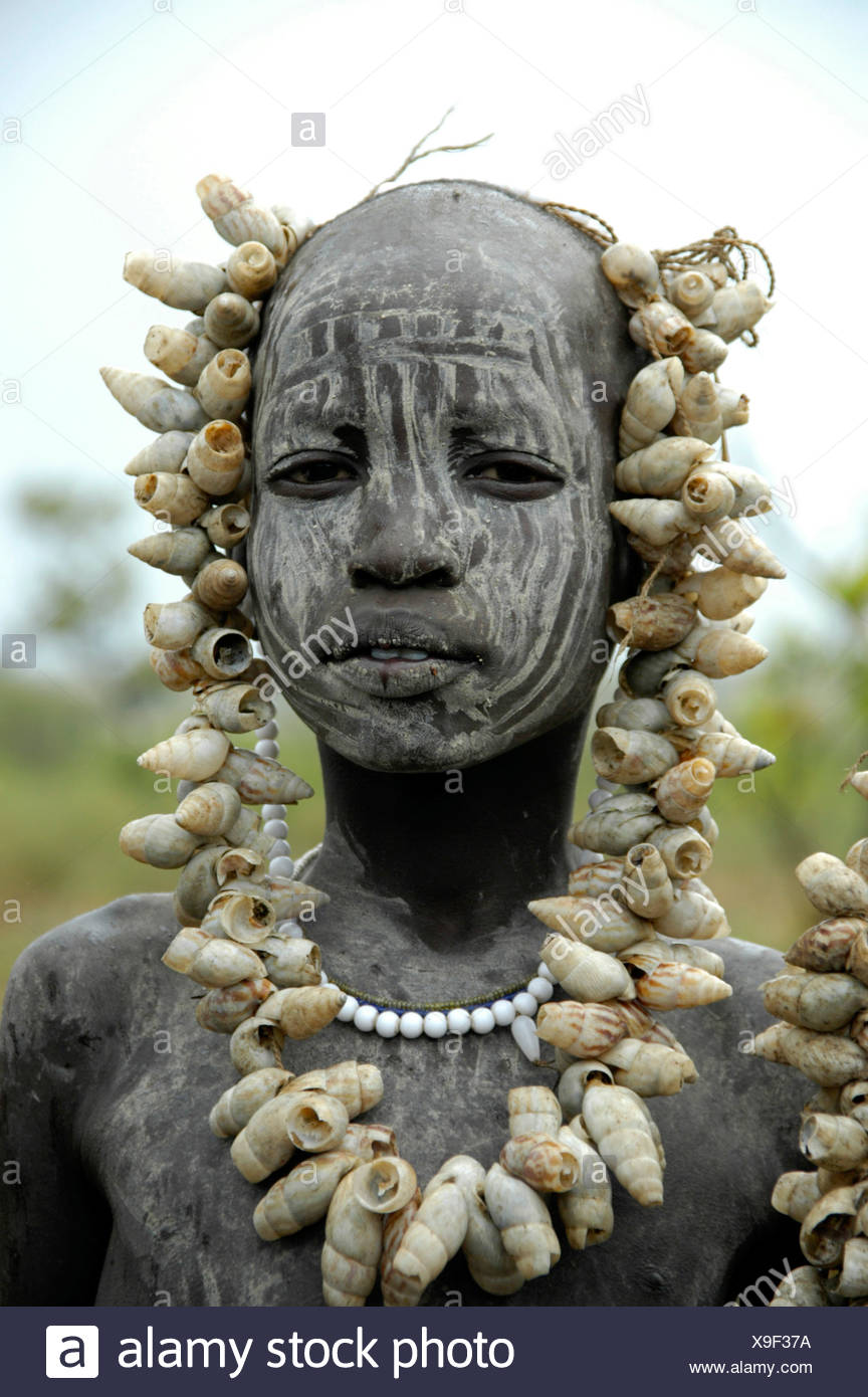Portrait of a girl of the Mursi tribe, face painted white, big necklace made of shells, near Jinka, Ethiopia, Africa - Stock Image