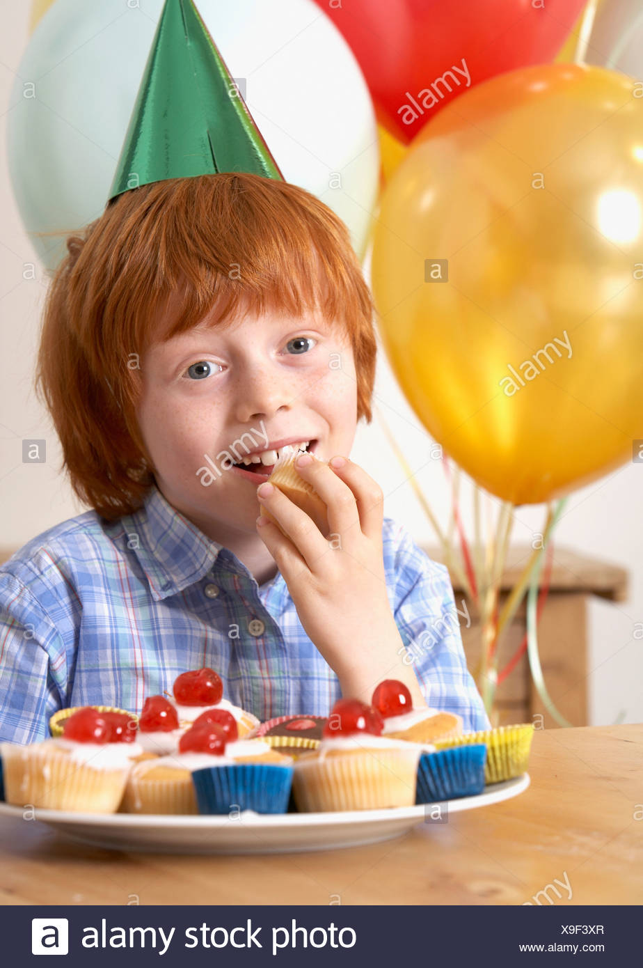 Young boy at birthday party eating a cupcake - Stock Image