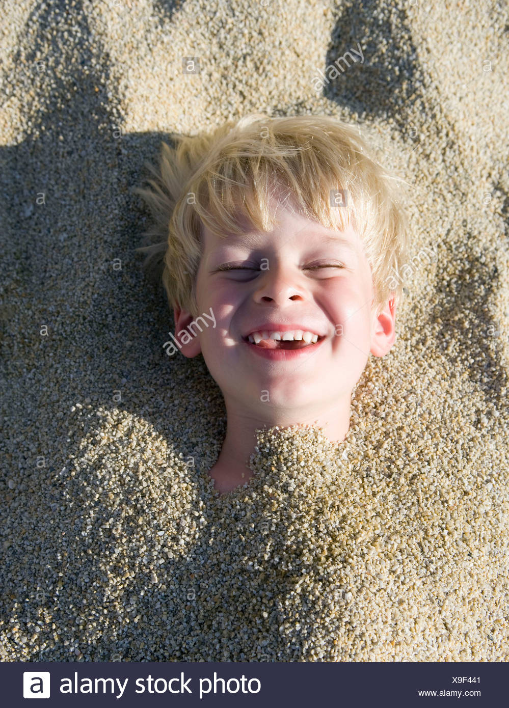 Young boy buried in the sand laughing. Stock Photo