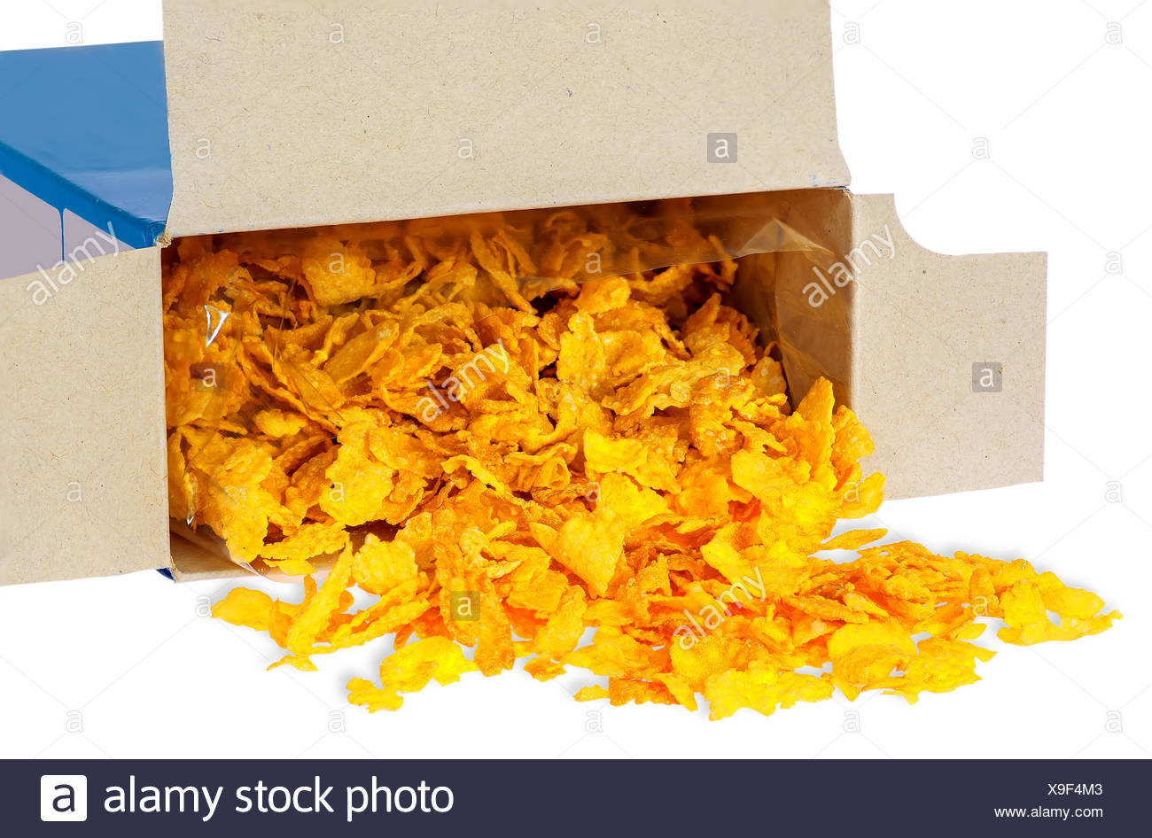 Corn flakes spill out of cardboard box - Stock Image